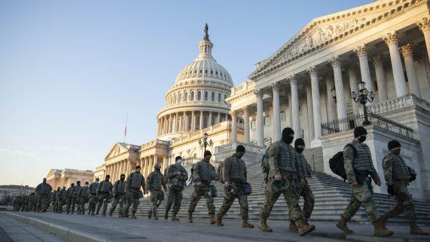 Des membres de la Garde nationale marchent devant le bâtiment du Capitole américain à Washington, DC mercredi.  Photographie: Sarah Silbiger / Bloomberg