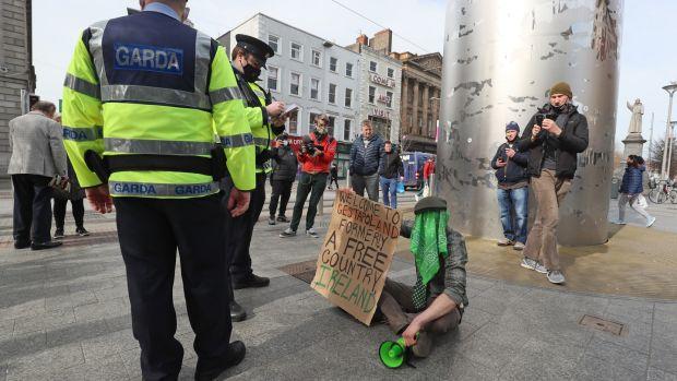 Garda s'adresse à un manifestant solitaire sur O'Connell Street dans le centre-ville de Dublin avant une manifestation anti-lockdown prévue mercredi.  Photographie: Brian Lawless / PA Wire
