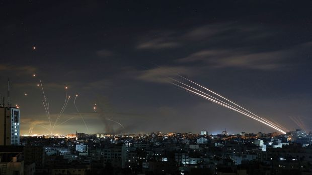 Le système israélien de défense antimissile Iron Dome (à gauche) intercepte les roquettes tirées par le mouvement Hamas depuis la ville de Gaza vers Israël tôt dimanche.  Photographie: Mohammed Abed / AFP via Getty