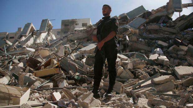 Un policier se tient sur les décombres d'un bâtiment abritant le bureau de l'Associated Press et d'autres médias dans la ville de Gaza qui a été détruit après que des avions de combat israéliens l'ont démoli samedi.  Photographie: Hatem Moussa / AP