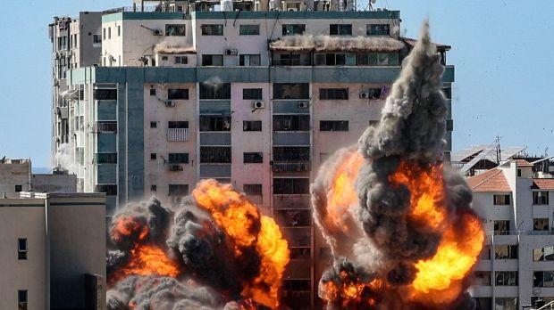 Une boule de feu jaillit de la tour Jala, qui abritait la télévision al-Jazeera basée au Qatar et l'agence de presse Associated Press, alors qu'elle est détruite lors d'une frappe aérienne israélienne à Gaza, samedi.  Photographie: Mahmud Hams / AFP via Getty